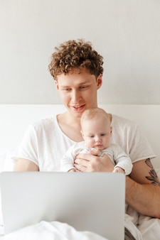 Happy young father playing with his little baby son while working on a laptop computer, laying in bed