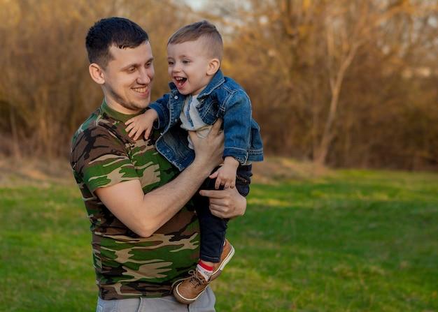 Счастливый молодой отец, играя с сыном на открытом воздухе.