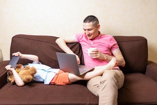 Счастливый молодой отец сидит на компьютере, используя ноутбук с сыном