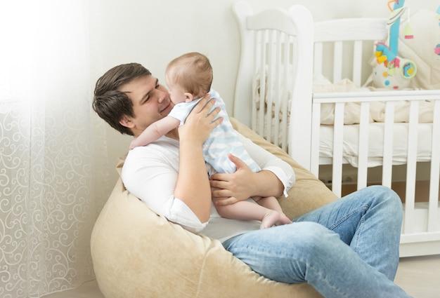 행복한 젊은 아버지는 가방 의자에 앉아 6개월 된 아들과 놀고 있습니다.