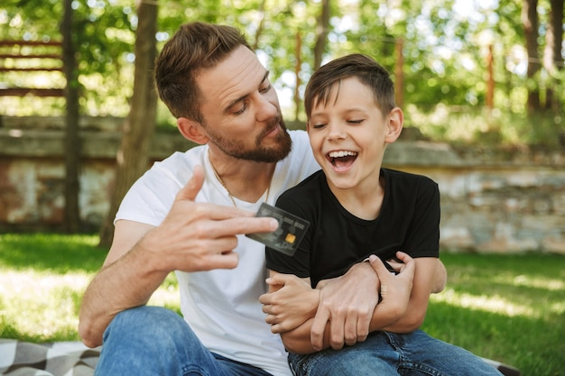 Happy young father sitting with his little son holding credit card.