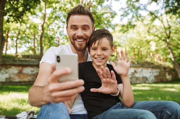 Счастливый молодой отец, сидя со своим маленьким сыном с помощью мобильного телефона.