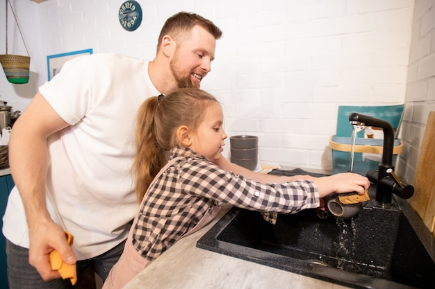 Happy young father standing by his little daughter and helping her to wash cup over sink in the kitchen after breakfast or dinner