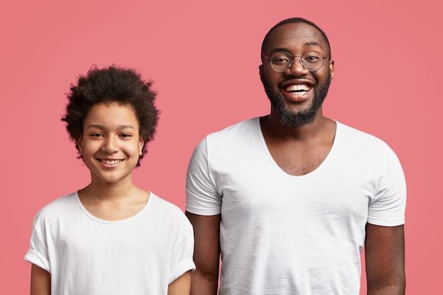 幸せな若い父親は彼の幼い息子の近くに立って、機嫌が良く、広い笑顔を持ち、ピンクの壁に隔離されたゲストを見て喜んでいます