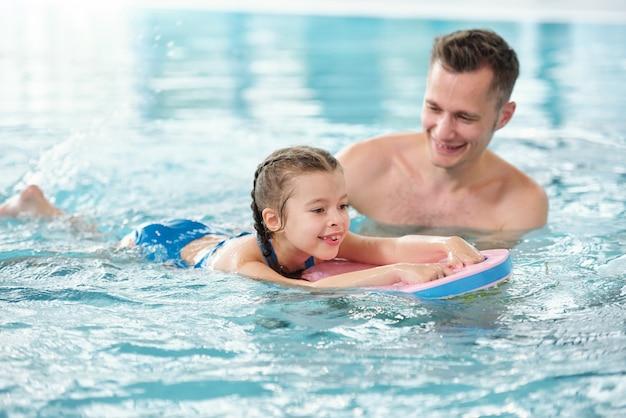 Счастливый молодой отец учит свою очаровательную маленькую дочь плавать в бассейне, проводя время или отдыхая в спа-центре или на летнем курорте