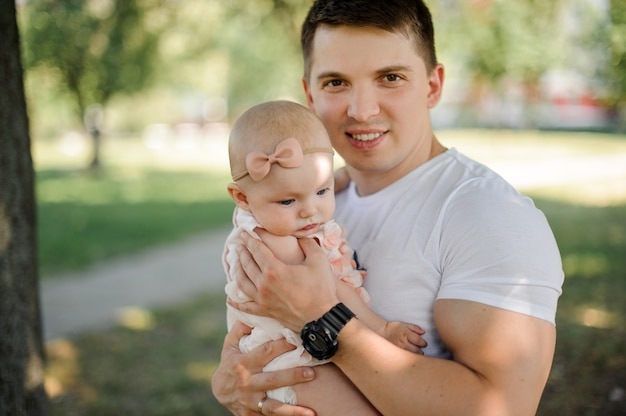 Happy young father walking with cute baby girl in park