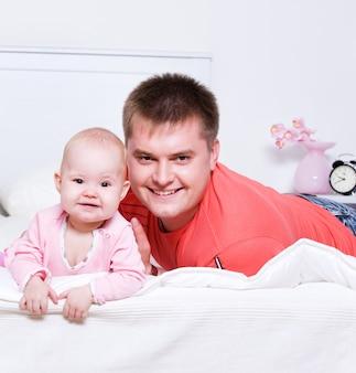 Счастливый молодой отец с улыбающимся ребенком, лежа на кровати в спальне