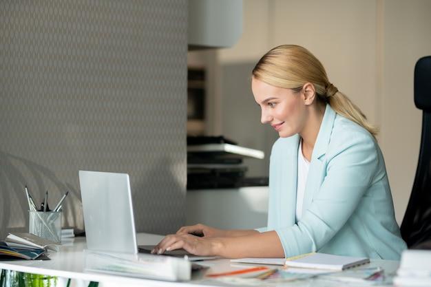 온라인 데이터를 읽거나 정보를 입력하는 동안 노트북 디스플레이를보고 행복 젊은 여성 디자이너