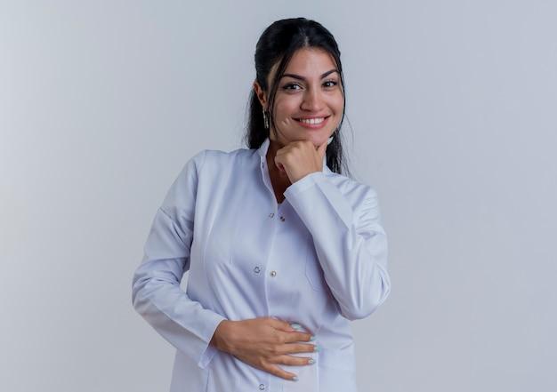 의료 가운을 입고 행복 한 젊은 여성 의사 감동 턱과 배꼽 절연 찾고