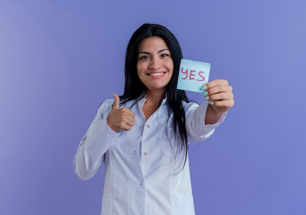 Happy young female doctor wearing medical robe showing yes note, looking showing thumb up