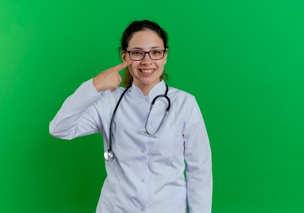 Happy young female doctor wearing medical robe and stethoscope and glasses  pointing finger on cheek isolated on green wall with copy space