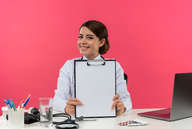 Felice giovane donna medico indossando abito medico e stetoscopio seduto alla scrivania con strumenti medici e laptop mostrando appunti isolati
