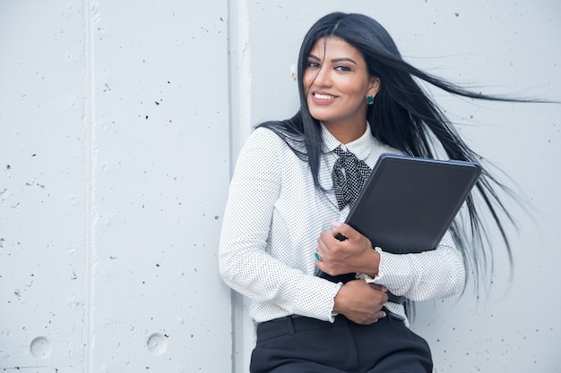 Happy young female entrepreneur with laptop