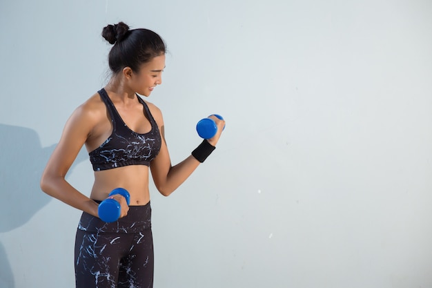 Happy young female fitness woman lifting dumbbells smiling and energetic.