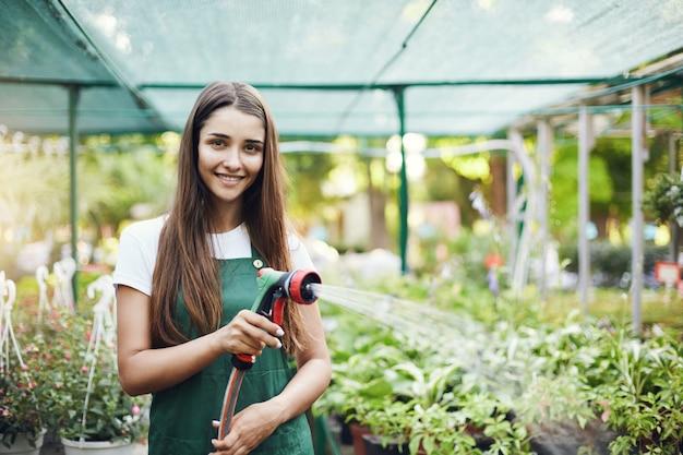 소유자 운영 온실 저장소에 식물을 급수하는 행복 한 젊은 여성 정원사.