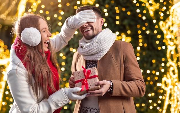 Счастливая молодая женщина смеется и закрывает глаза мужчине, даря подарочную коробку парню возле освещенной рождественской елки зимой