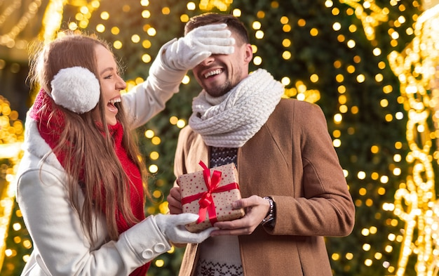 Happy young female laughing and covering eyes of male while giving gift box to boyfriend near illuminated christmas tree in winter
