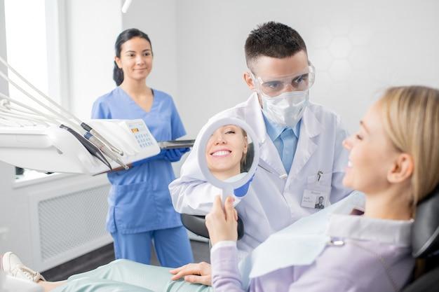 Счастливая молодая пациентка с зубастой улыбкой смотрит в зеркало, сидя в кресле в стоматологическом кабинете со своим стоматологом впереди