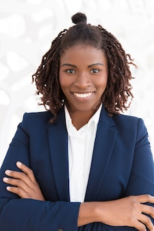 Happy young female professional posing with arms folded