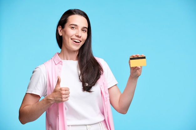Счастливая молодая женщина-шопоголик показывает жест вверх пальцем и пластиковую кредитную карту изолированно