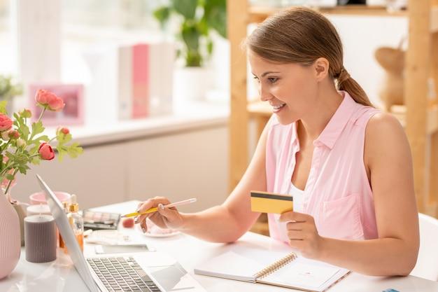 オンライン商品を選択しながらラップトップのディスプレイを指すプラスチックカードで幸せな若い女性の買い物中毒者