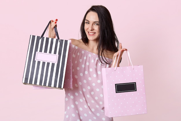 Happy young female shopaholic with pleased facial expression, dressed in summer polka dot dress, holds shopping bags, rejoices buying new clothes, poses on rosy. woman with packages