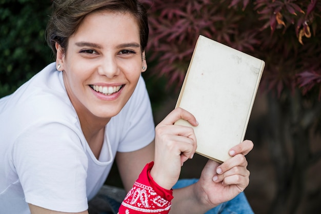 Happy young female showing book