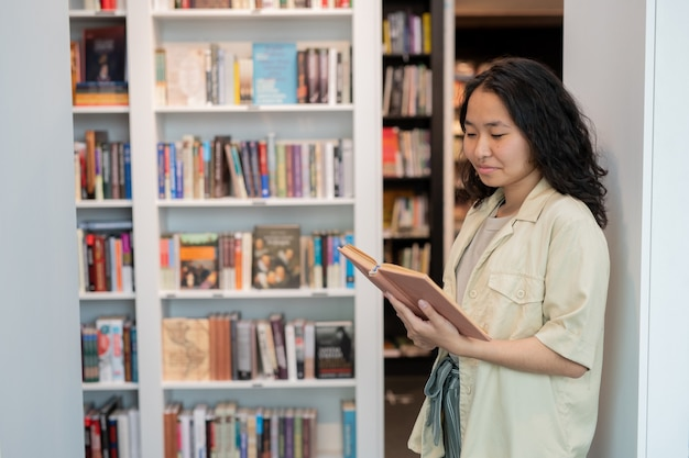Happy young female student looking at text in open book