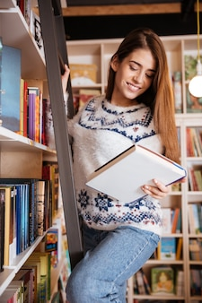 Happy young female student taking book from shelf in library