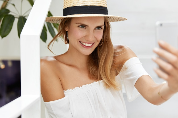 Happy young female tourist recreate at hot country, makes selfie on cell phone. woman blogger wears summer hat and blouse makes online translation, tells something to followers