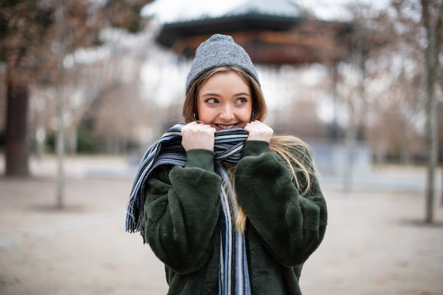 Happy young female in warm clothes wrapping in scarf and looking away in autumn park on really cold day