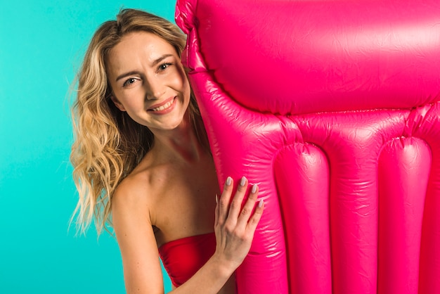 Happy young female with inflatable mattress