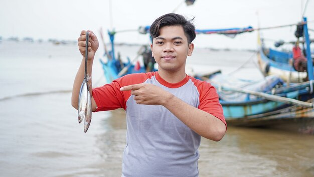 彼のキャッチフィッシュと彼のボートの前でショーを保持しているビーチで幸せな若い漁師