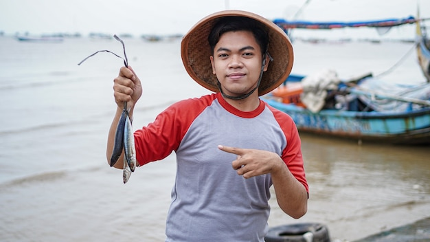 그의 캐치 물고기를 들고 해변에서 행복 한 젊은 어부와 그의 보트 앞에 보여줍니다