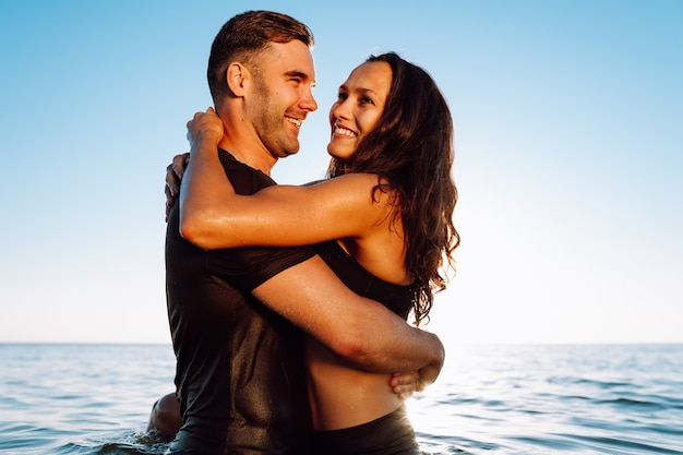 Happy young fit couple in the sea or ocean hug each other with love at summer sunset. romantic mood, tenderness, relationship, vacation concept.-