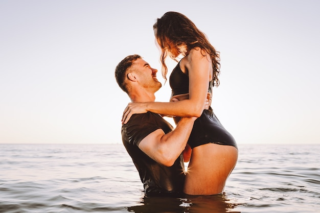 Happy young fit couple in the sea or ocean hug each other with love at summer sunset. romantic mood, tenderness, relationship, vacation concept.