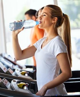 행복 한 젊은 맞는 여자 운동 중 음주, 체육관에서 실행. 건강, 스포츠, 사람 개념