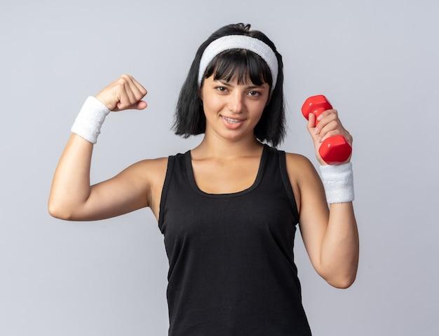 Felice giovane ragazza fitness che indossa la fascia che tiene il manubrio facendo esercizi alzando il pugno che mostra i bicipiti bi