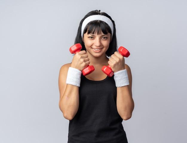 Felice giovane ragazza di forma fisica che indossa la fascia tenendo i manubri facendo esercizi guardando fiducioso sorridente in piedi su sfondo bianco