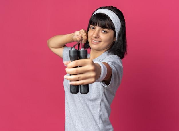Felice giovane ragazza fitness che indossa la fascia tenendo la corda per saltare guardando la telecamera con un sorriso sul viso in piedi su sfondo rosa