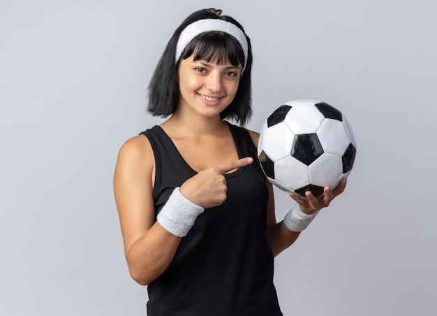 Felice giovane ragazza di forma fisica che indossa la fascia che tiene il pallone da calcio che punta con il dito indice su di esso sorridendo allegramente guardando la telecamera in piedi su sfondo bianco