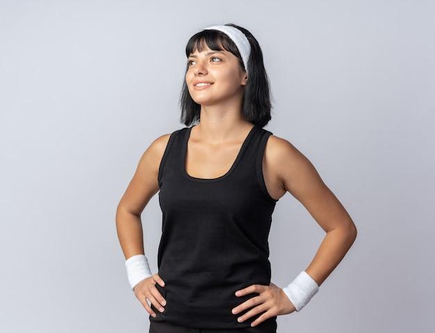 Felice giovane ragazza fitness che indossa la fascia guardando in alto sorridendo allegramente in piedi su sfondo bianco
