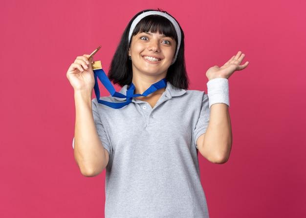Felice giovane ragazza fitness che indossa fascia con medaglia d'oro intorno al collo guardando la telecamera sorridendo allegramente in piedi sopra il rosa
