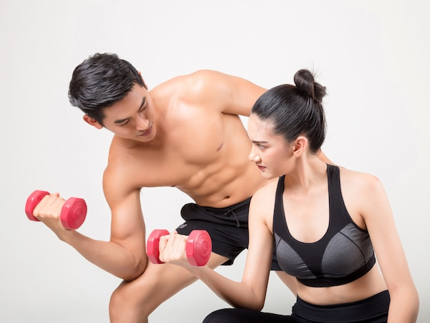 Happy young fitness  man and his girlfriend in training time . fitness and healthy lifestyle concept. studio shot on white background.