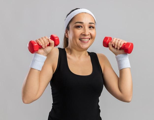 Felice giovane donna fitness con fascia che tiene il manubrio facendo esercizi guardando fiducioso sorridente in piedi sul muro bianco