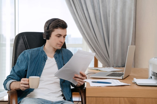 Happy young freelancer in headphones working remotely from home office