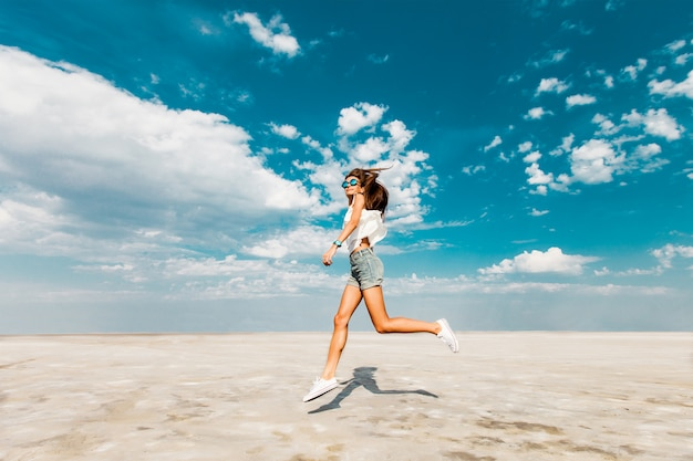 Happy young fresh slim athletic girl runs along the beach in trendy jeans shorts and white sneakers. blue sky in the clouds, summer sunny mood.