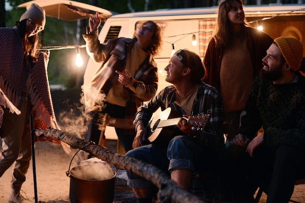 Happy young friends dancing and singing songs with guitar during camping in the forest