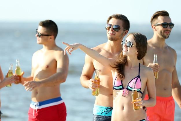 Счастливые молодые друзья пьют пиво на пляже, на открытом воздухе