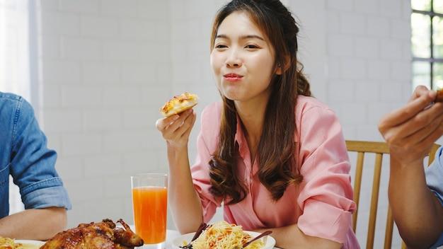 家で昼食を食べて幸せな若い友人グループ。アジアの家族のパーティーでピザ料理を食べたり、家で一緒にダイニングテーブルに座って食事を楽しみながら笑ったりします。お祝いの休日と一体感。